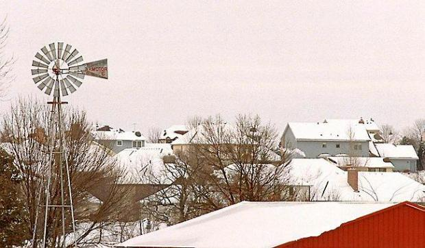 A windmill on a farm looms over a housing development along Woodlane Drive in Woodbury.