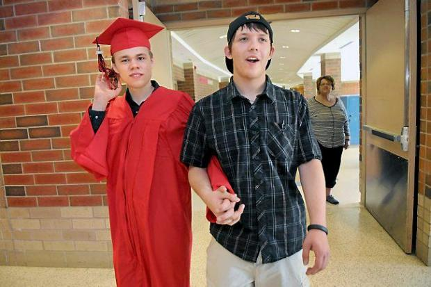 Devin Wildes, left, and Nick Dinzeo walk hand-in-hand to Devin's graduation ceremony at Stillwater Area High School Friday May 30, 2014.