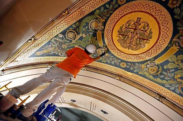 An artist from Conrad Schmitt Studios uses decorative painting to repair deterioration to a mural Aug. 18 in the House chambers as restoration of the Minnesota State Capitol continues in St. Paul, Minn. Renovators planned to spend $4.5 million on furniture and decorative finishing touches on the inside until House Republicans quietly pushed to bump up the furnishings allocation by $2 million, or 45 percent. (AP Photo/Jim Mone)