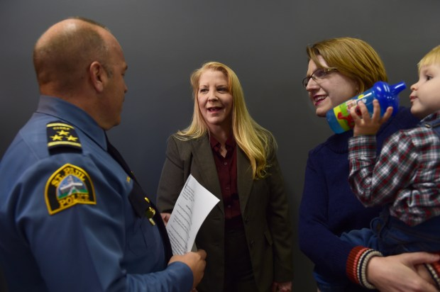 Former St. Paul Police officer Felicia Reilly, center, talks with St. Paul Police Chief Todd Axtell, left, before a ceremony recognizing and awarding her for years of service at the St. Paul Police Federation office in St. Paul on Wednesday, Nov. 2, 2016. At right is Reilly's daughter, Theresa Paulsen, holding her son, Miles. (Pioneer Press: Scott Takushi)