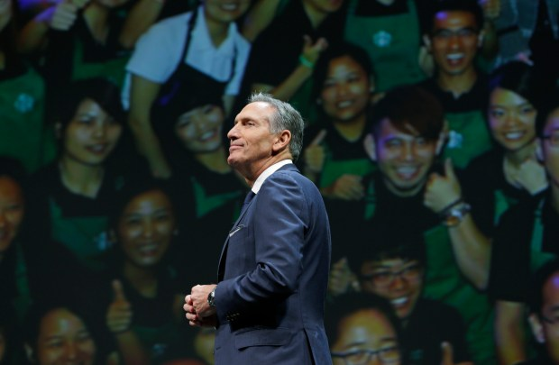 FILE - In this Wednesday, March 23, 2016, file photo, Starbucks CEO Howard Schultz walks in front of a photo of Starbucks baristas, at the coffee company's annual shareholders meeting in Seattle. Starbucks announced Thursday, Dec. 1, 2016, that Schultz is stepping down from the coffee chain that he joined more than 30 years ago, and that Kevin Johnson will become chief executive as of April 3, 2017. Schultz will become executive chairman on that date to focus on innovation and social impact activities, among other things. (AP Photo/Ted S. Warren, File)