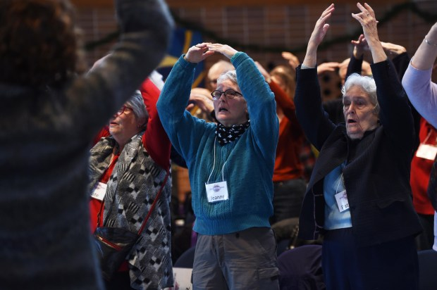 Jeanne LaBore, center, and her mother, Patricia McGuire, right, practice with the Giving Voice Chorus, made up of older adults facing Alzheimer's and other forms of memory loss, as they rehearse for their upcoming concert at the Minnesota History Center, Monday, December 5, 2016.  (Pioneer Press: Scott Takushi)