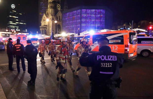 Firefighters walk past ambulances after a truck ran into a crowded Christmas market and killed several people in Berlin, Germany, Monday, Dec. 19, 2016. (AP Photo/Michael Sohn)