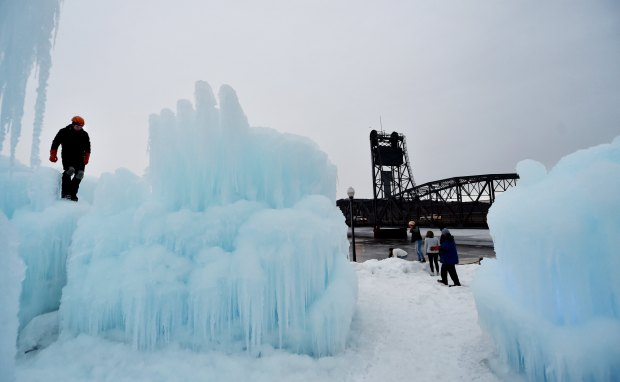 While a worker creates an ice tower, sightseers move in for a better look at the Stillwater ice castle on Dec. 30, 2016. The gigantic formation in downtown Stillwater's Lowell Park is scheduled to open to the public Jan. 6. (Pioneer Press archive: John Autey)