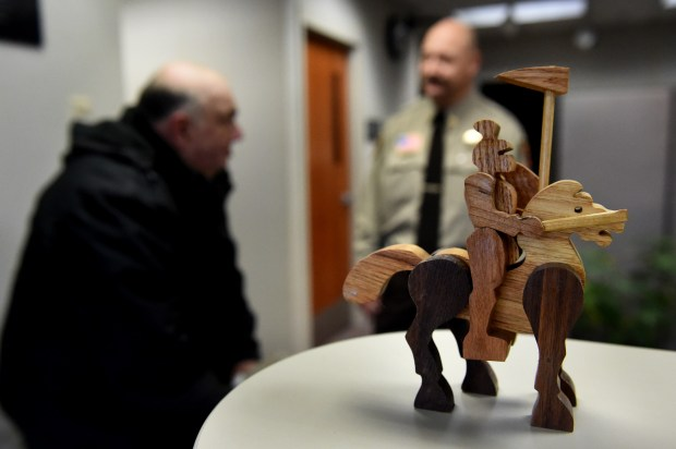 Phil Lagarde of Stillwater talks to Washington County Jail Commander Roger Heinen after delivering handmade wooden toys to the jail Wednesday, Dec. 7, 2016. Lagarde used 14 pieces of wood, including black walnut, cherry, hard maple and oak, to make the 10-inch-tall knight and horse. (Pioneer Press: Jean Pieri)