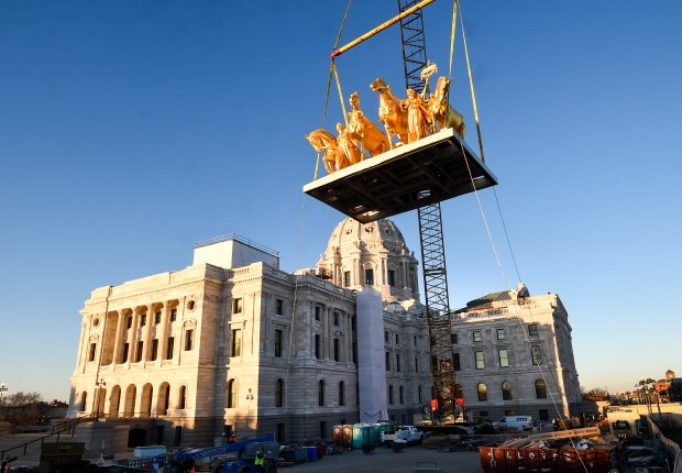 The Quadrigra glints in the morning light as a crane returns the five-ton sculpture to its spot on the Minnesota Capitol early Saturday, Nov. 12, 2016. Conservators restored the sculpture, which was removed from the Capitol last May for roof repairs. (Special to the Pioneer Press: Craig Lassig)