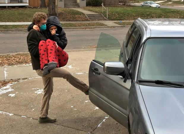 Scott Watkins carefully maneuvers his wife, Johanna Watkins, into their car for the trip to the hospital. (Brett Boese/Post-Bulletin)