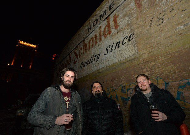 Max Boeke, left, Craig Cohen and Jordan Standish pose in front of one of the out buildings at the old Schmidt Brewery on West Seventh Street in St. Paul on Thursday, Jan 12, 2017. The trio are bringing beer brewing back to the landmark brewery. (Pioneer Press: John Autey)