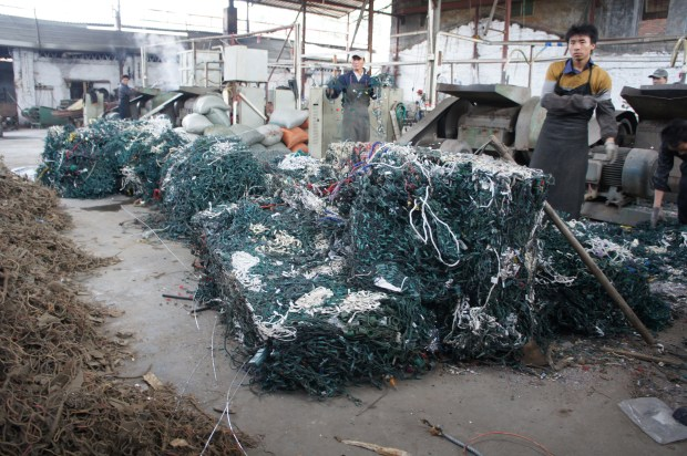 Bales of imported U.S. Christmas tree lights, ready to be recycled at Raymond Li's Christmas tree light recycling factory in Shijao, China. (Photo by: Adam Minter)