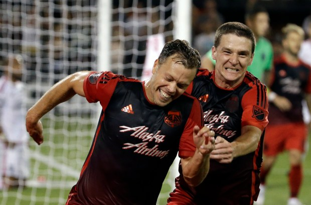 FILE - In this July 5, 2015, file photo, Portland Timbers defender Jack Jewsbury, left, celebrates his goal during extended play with teammate Will Johnson in an MLS soccer game against the San Jose Earthquakes in Portland, Ore. Jewsbury announced Sunday, Sept. 18, 2016, that he will retire at the end of this season after 14 seasons in Major League Soccer. (AP Photo/Don Ryan, File)
