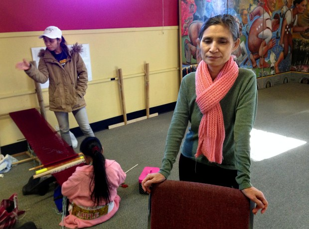 Shi Paw of St. Paul is pictured after a traditional Karen weaving class at the East Side Freedom Library in St. Paul on Feb. 1, 2017. Shi Paw has lived in St. Paul since 2011, when she left a Karen refugee camp in Thailand and came to the U.S. with five of her seven children. Her eldest daughter had planned to join her in St. Paul in 2017, but a travel ban signed by President Donald Trump has delayed their reunion indefinitely. Trump's executive order bans all refugees from entering the country for 120 days, by which time her daughter's security clearances may have expired. Pictured in the background is her younger daughter, Lay Paw, 23, and a traditional Karen weaver. (Pioneer Press: Frederick Melo)