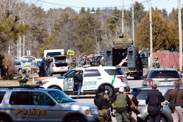 Numerous law enforcement vehicles and SWAT teams respond to shooter Wednesday, March 22, 2017, at an apartment complex in Rothschild, Wis. The shootings happened at a bank, a law firm and an apartment complex, where officers, including a SWAT team, were in a standoff with the suspect late in the afternoon, Wausau police Capt. Todd Baeten said at a news conference. The area is about 90 miles west of Green Bay. (T'xer Zhon Kha /The Post-Crescent via AP)