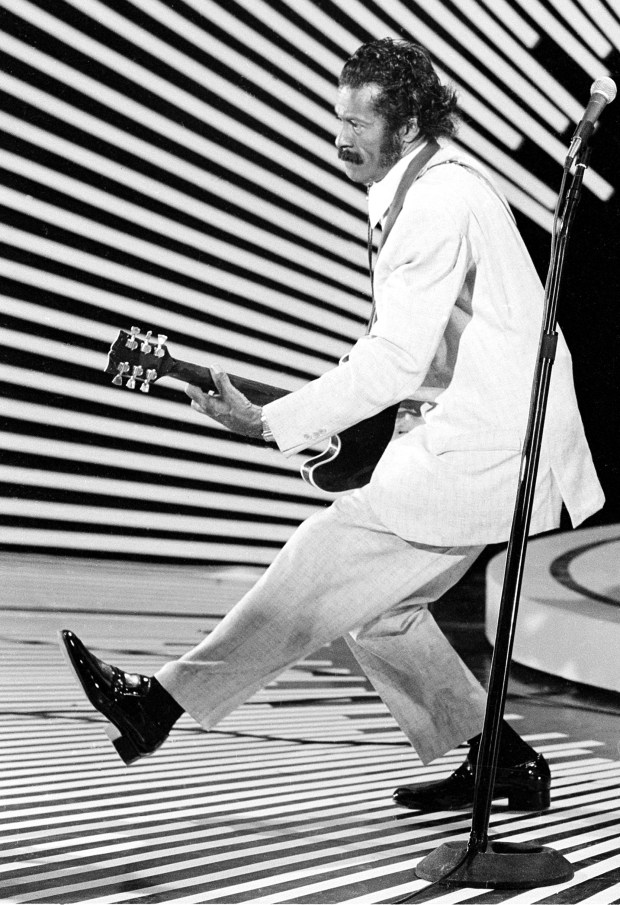 "In this April 4, 1980 photo, guitarist and singer Chuck Berry performs his ""duck walk"" as he plays his guitar on stage. On Saturday, March 18, 2017, police in Missouri said Berry has died at the age of 90. (AP Photo)"