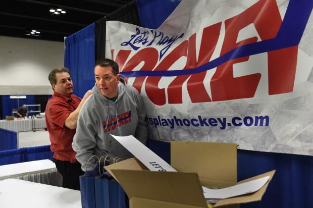 Bryan Zollman, right, the new owner of Let's Play Hockey newspaper, who is running the Let's Play Hockey Expo at River Centre in St. Paul, puts up a sign with Mark Terry on Thursday, March 9, 2017. Zollman was a junior winger on the 1991 state champion Hill-Murray Pioneers team and he scored the game-tying goal in the title game against Duluth-East. He read the weekly Lets Play Hockey newspaper as a child. (Pioneer Press: Jean Pieri)