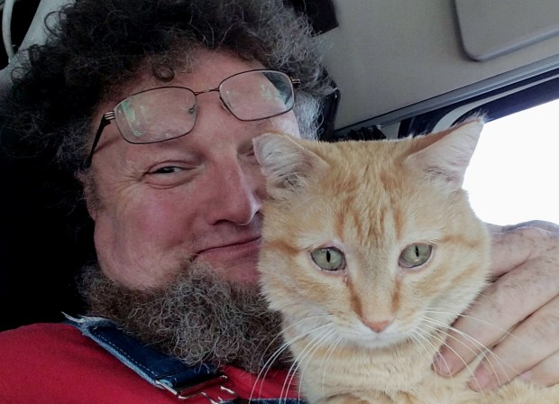 This August 2016 photo provided by Paul Robertson shows Robertson posing with his cat Percy in St. Paul, Minn. Robertson, a long-haul semitrailer driver, was reunited with his cat during a delivery in Shoals, Ind., on Feb. 25, 2017, after the cat survived a trip of 400 miles by clinging to the undercarriage of his semi. Robertson thought he had lost his traveling companion at a rest stop in Ohio and was astonished when the cat wandered out from under the truck in Indiana. (Paul Robertson via AP)