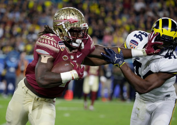 Florida State running back Dalvin Cook, left, runs by Michigan safety Delano Hill during the Orange Bowl on Dec. 30, 2016, in Miami Gardens, Fla. (AP Photo/Lynne Sladky, File)