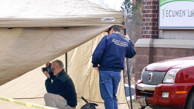 Duluth, Minn., police investigator Dan Salatel takes pictures at the scene of a fatal pedestrian-SUV crash at 40th Avenue and London Road on Tuesday, April 4, 2017. The 62-year-old female victim was hit by the Mercury Mountaineer to the right of Salatel. A 49-year-old woman was driving the SUV and was later jailed on suspicion of criminal vehicular homicide. (Steve Kuchera / Forum News Service)