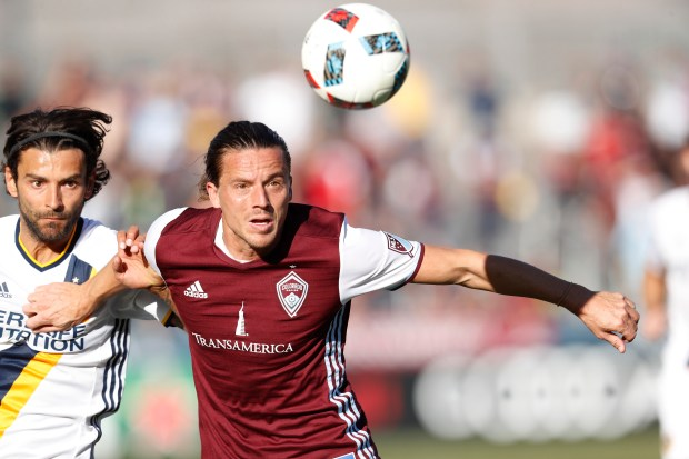 Los Angeles Galaxy midfielder Baggio Husidic, left, and Colorado Rapids defender Marc Burch pursue the ball in the second half of a second leg soccer match of the Western Conference semifinals of the MLS cup playoffs in Commerce City, Colo., on Sunday, Nov. 6, 2016. Colorado won 1-0 and advances to the next round of the playoffs. (AP Photo/David Zalubowski)