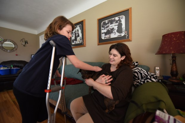 Maddi Vance, 9, leans over her crutches to pet the family dog Dottie, held by her mother, Jill Marie Rodriques, inside a relative's home in St. Paul, Minn., Wednesday, April 19, 2017. Maddi, her brother Gage, 7, a third child and a school staff member were all struck by a car while crossing the street Monday around 4 p.m. at White Bear and Case avenues. With a broken toe and pinched nerve, Maddi suffered the most serious injuries.(Pioneer Press / Dave Orrick)