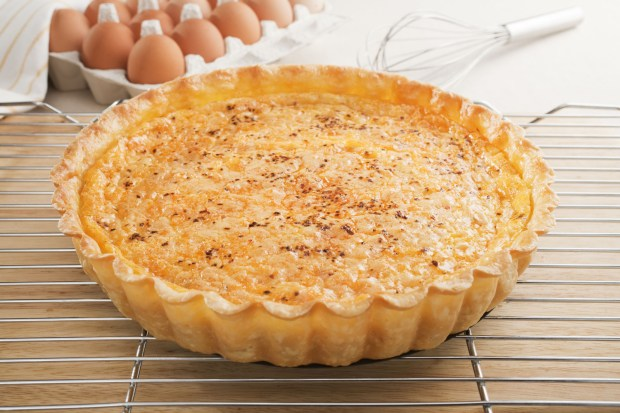 To serve, use a sharp, serrated knife to cut the warm quiche into wedges. (Dreamstime.com)