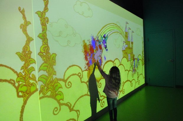"Aubree Asaro, 5, reaches to touch a digital unicorn that she colored at the ""Art Alive"" station. Her work is projected onto a wall mural at the Crayola Experience at the Mall of America on Thursday, May 25, 2017. The Crayola Experience offers interactive stations centered around crayons. Kids can engage at the various stations with what they have drawn. The exhibit is celebrating its one-year anniversary. (Ginger Pinson / Pioneer Press)"