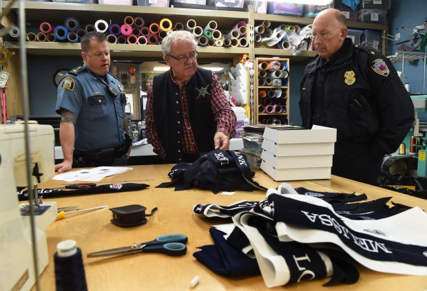 St. Paul Police Senior Cmdr. Axel Henry, left, St. Paul Police Historial Society President Ed Steenberg, middle, and Maplewood Police Chief Paul Schnell check out the honor ribbons for fallen police officers, which were embroidered at Corporate Mark in St. Paul, April 26, 2017. (Scott Takushi / Pioneer Press)