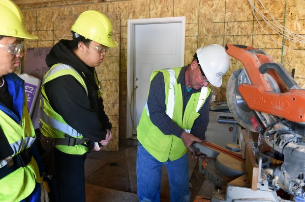 Carpentry instructor Perry Franzen, right, shows St. Paul College students Chou Lee, left, and Kong Meng how to properly adjust a mitre box as the students build a house in Vadnais Heights on Tuesday, May 9, 2017. St. Paul College has a year-long carpentry program and a cabinet making program that provides trained students to the construction industry.  (Scott Takushi / Pioneer Press)