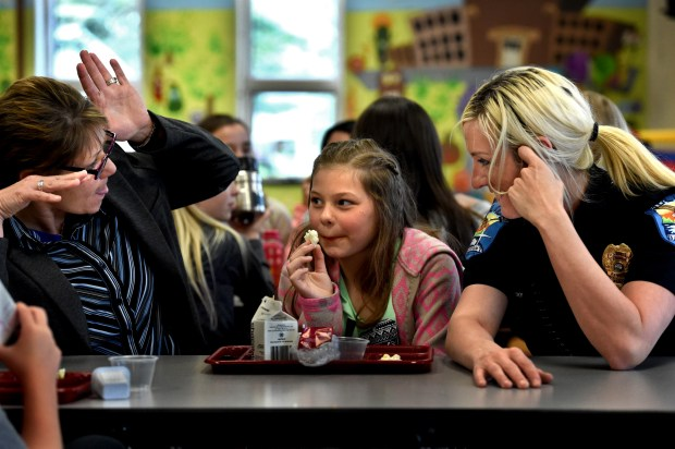 """Bayport Police Chief Laura Eastman, left, and Officer Brittany Lepowsky, right, goof around during lunch with Jenna Ellis, 10, at Anderson Elementary School in Bayport on Thursday, April 27, 2017. """"It's like she has grown up some since doing that. We are seeing positives come out of this. You need a village to raise kids,"""" said Jenna's grandmother, Jan Ellis. (Jean Pieri / Pioneer Press)"""