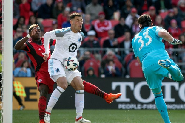 Minnesota United FCs Christian Ramirez, center, scores an own goal under pressure from Toronto FC's Chris Mavinga, left, after Minnesota United goalkeeper Bobby Shuttleworth (33) failed to deal with a cross during the second half of an MLS game in Toronto on Saturday, May 13, 2017. (Chris Young/The Canadian Press via AP)