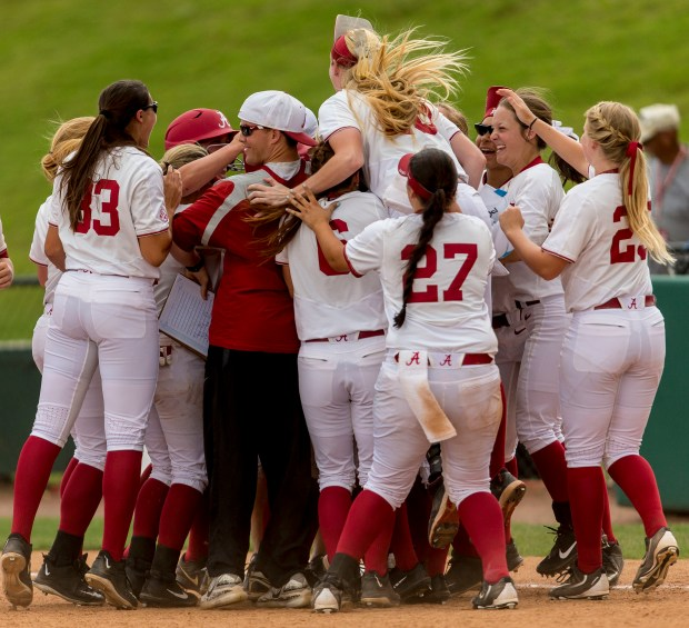 Alabama's Reagan Dykes is mobbed by teammates after her game winning bases-loaded walk against Minnesota in the NCAA regional softball tournament, Saturday, May 20, 2017, at Rhoads Stadium in Tuscaloosa, Ala. Alabama won 1-0. (Vasha Hunt/AL.com via AP)