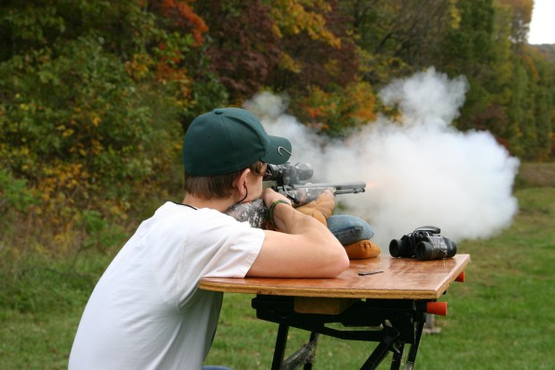 A Muzzle Loader Rifle emits smoke and fire as it is fired from a shooting bench with fall colors in the background.