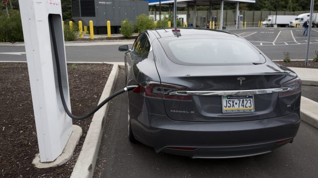 A Tesla electric car is recharged at a Tesla Motor Supercharging station at a rest stop on Interstate 95 in Darien, Conn., Sept. 18, 2016. (AP Photo/Mark Lennihan)