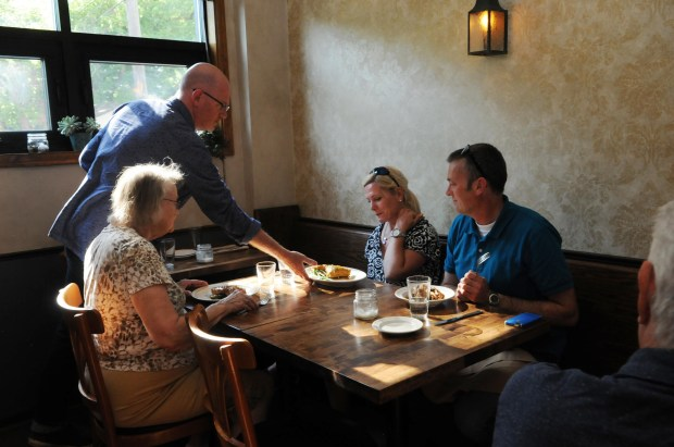 Bar Brigade owner Matty O'Reilly serves dinner to Lara Holland, center, her husband, Vern Nichols and his mother, Muriel Nichols, on Tuesday, June 21, 2017. (Ginger Pinson / Pioneer Press)