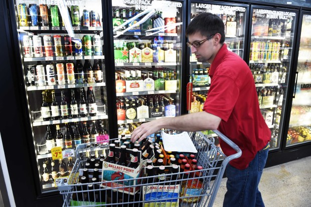 Troy Leistikow, store manager of Village Wine & Spirits in Lakeland, Mn. gets ready for a busy holiday weekend by pulling beer and wine to put on sale, Wednesday, June 28, 2017. Leistikow is happy that his store is finally able to sell liquor on Sundays, beginning July 2, and can compete with Wisconsin stores not far away. (Scott Takushi / Pioneer Press)