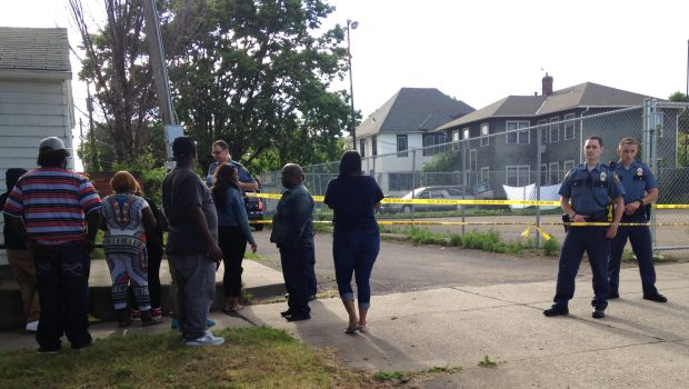 Onlookers gather as police keep watch Saturday afternoon, June 24, 2017, in the area of Aurora Avenue and Marion Street in St. Paul, where a man was shot and killed. White sheets in the background obscure the body from view. (Mara Gottfried / Pioneer Press)