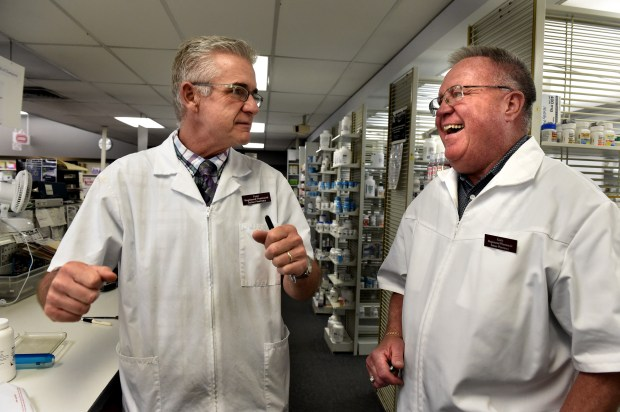 Gary Raines, 71, right, listens to longtime pharmacist Peter Haas, who has worked with Raines for 40 years, tell a story at Setzer's Pharmacy on Rice Street in St. Paul on Friday, June 30, 2017. Raines will be retiring. He started there as a freshman in college in 1966. He took over in 1989, and in 1994 he officially took over on paper. (Jean Pieri / Pioneer Press)