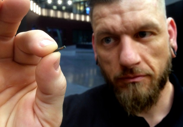 "Self-described ""body hacker"" Jowan Osterlund from Biohax Sweden, holds a small microchip implant, similar to those implanted into workers at the Epicenter digital innovation business centre during a party at the co-working space in central Stockholm, Tuesday March 14, 2017. Microchips are being implanted into volunteers to help them open doors and operate office equipment, and its become so popular that members of the Epicentre cyborg club hold regular parties for those with the tiny chips embedded in their hands. (AP Photo/James Brooks)"