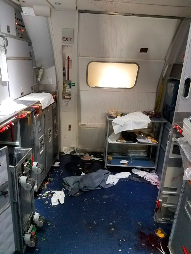 This Friday, July 7, 2017 photo taken the FBI and released via the U.S. Attorney's Office in Seattle shows the aftermath of a cabin on Delta Flight 129 from Seattle to Beijing, after authorities say flight attendants struggled with Joseph Daniel Hudek IV, a passenger who lunged for an exit door. The photo was included in a criminal complaint filed Friday, July 7. The passenger is charged with interfering with a flight crew and faces up to 20 years in prison. (FBI via U.S. Attorney's Office in Seattle via AP)