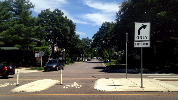 Bollards, road markings, street signage and a bike-only crossing through a central median crossing mark the Charles Avenue Bicycle Boulevard at Lexington Parkway in a July 2017 photo. (Frederick Melo / Pioneer Press)