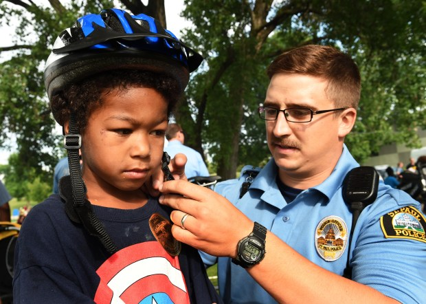 St. Paul Police officer Andy Kempe fits Landon Wynn, 5, with a bike helmet as part of a new program called Bike Cops for Kids, at St. Paul's Conway Rec Center on June 29, 2017. Modeled after a program in Minneapolis, officers give bike helmets to children they encounter and teach them about bike safety. (Scott Takushi / Pioneer Press)