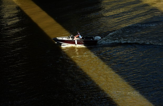 Boaters pass through a strip of sunlight framed by the darkness of the Wabasha Street Bridge's shadow on the Mississippi River near downtown St. Paul, Monday, July 3, 2017. (Scott Takushi / Pioneer Press)