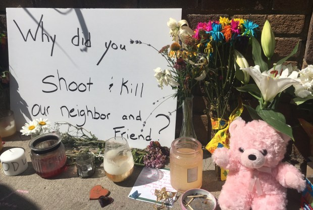 """Why did you shoot and kill our neighbor and friend?"" reads a sign where tributes to Justine Damond have been collecting, at an alley west of Wentworth Avenue South on 51st Street in Minneapolis on Monday. Two days earlier, Minneapolis police shot and killed Damond after she called 911 to report an assault, according to the Minnesota BCA. (Lisa Legge / Pioneer Press)"