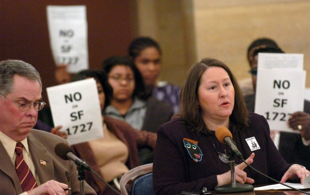 Michelle Gross, right, speaks in opposition to SF 1727, a bill before the Senate Committee on Crime Prevention and Public Safety, which would make it a crime to provide false information to a police officer, or to falsely report police misconduct, during a hearing in St. Paul in March 2004. Holding signs behind Gross, the Vice President of Communities United Against Police Brutality, are members of the same organization. At left front is Sen. Mike McGinn, R- Eagan, author of S.F. 1727. (Scott Takushi / Pioneer Press)