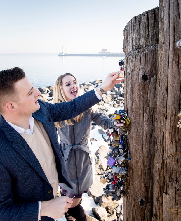 Chris Lewandowski and Shayna Derby place a love lock on a set of pilings along Lake Superior in Canal Park this winter. (Courtesy of Bryan Jonathan Weddings photo via Forum News Service)