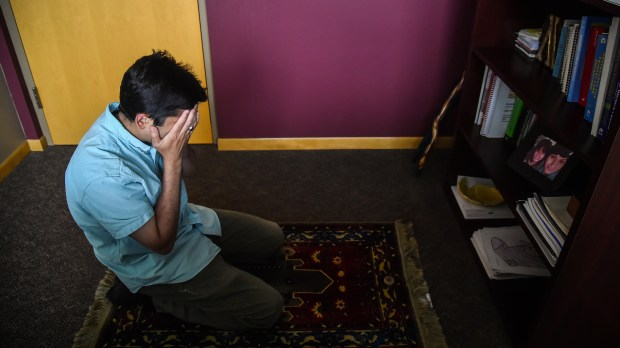 Dr. Ayaz Virji prays in his office after seeing a patient at the hospital where he works as a family medicine doctor, chief of staff and clinic medical director at Johnson Memorial Health Services in Dawson, Minn. (Salwan Georges, Washington Post)