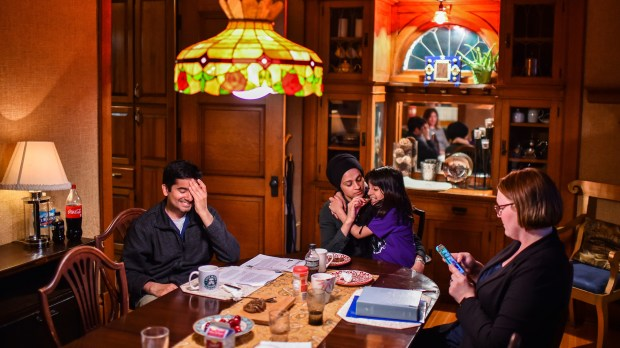 Dr. Ayaz Virji, 42, far left, reacts as his wife Musarrat Virji, 36, feeds their daughter Maya, 9, slices of dates while Pastor Mandy France checks her phone after preparing for the next day lecture. (Salwan Georges, Washington Post)