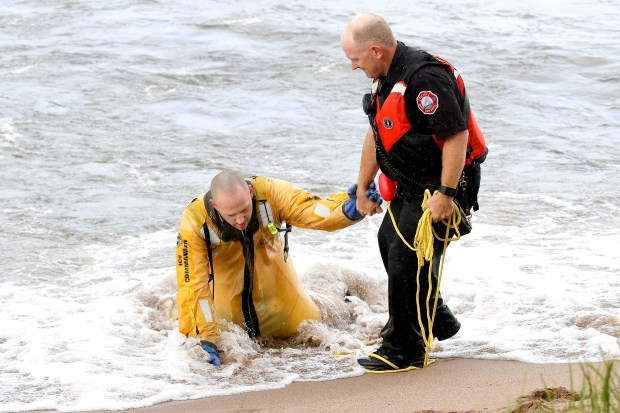 A Duluth firefighter helps another firefighter to shore after their rescue boat capsized after battling large waves on Lake Superior Thursday evening while searching for two missing swimmers near the Park Point Beach House in Duluth. The survival suit of the firefighter in the water filled with water making it difficult to reach shore. (Clint Austin / Forum News)
