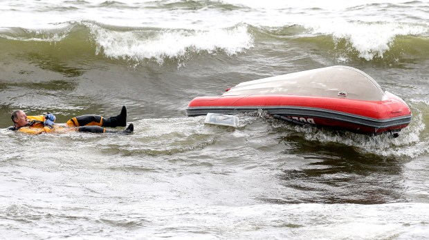 A Duluth firefighter floats in Lake Superior after a rescue boat capsized after battling large waves on Lake Superior Thursday evening while searching for two missing swimmers near the Park Point Beach House in Duluth. (Clint Austin / caustin@duluthnews.com)
