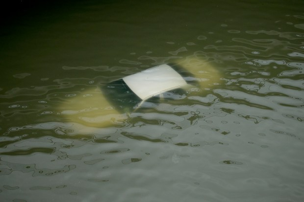 A car is submerged on a freeway flooded by Tropical Storm Harvey on Sunday, Aug. 27, 2017, near downtown Houston, Texas. The remnants of Hurricane Harvey sent devastating floods pouring into Houston on Sunday as rising water chased thousands of people to rooftops or higher ground. (AP Photo/Charlie Riedel)