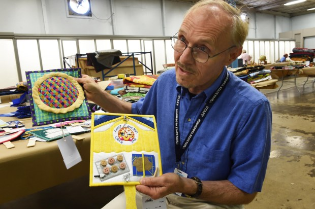 "Creative Activities superintendent Curt Pederson displays several of the Quilt-On-A-Stick entries, at the Minnesota State Fair on Aug. 15, 2017. This is the fifth year for the quilt-on-a-stick category, and the theme is ""Quilters Can Bake Too."" (Scott Takushi / Pioneer Press)"